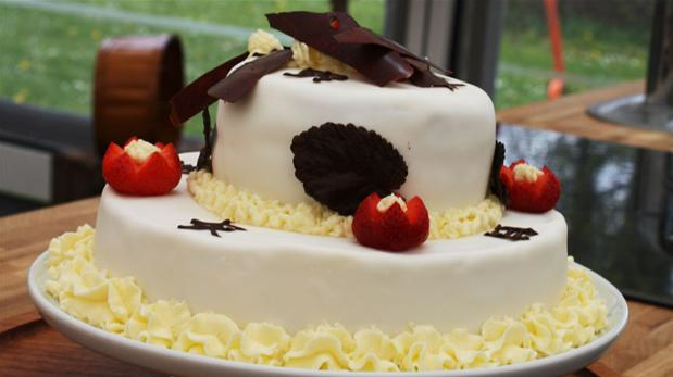 Billedet viser en lagkage overtrukket med hvid fondant og pyntet med chokolade og bær.