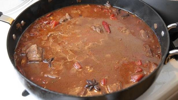Billedet viser en aromatisk gryderet med kalvekød, krydderurter og kanel.