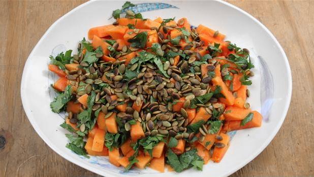 Billedet viser en tallerken anrettet med papayasalat med lime og græskarkerner.