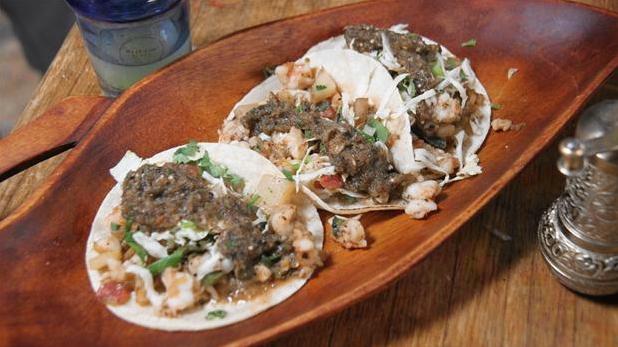 Billedet viser to færdige tacos med rejer, tomat, spidslkål og koriander.