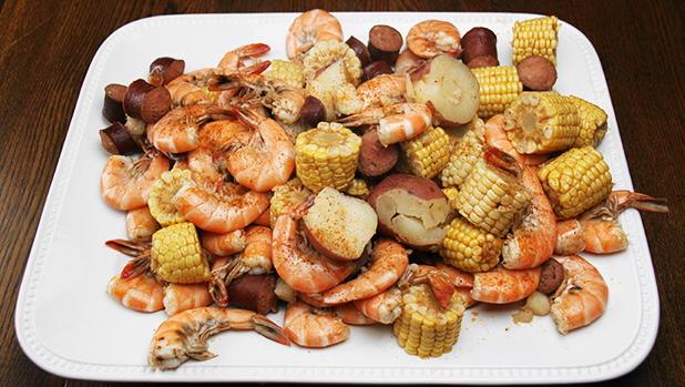 Billedet viser et skønt fad med Lowcountry Boil af tigerejer, majs og kartofler.