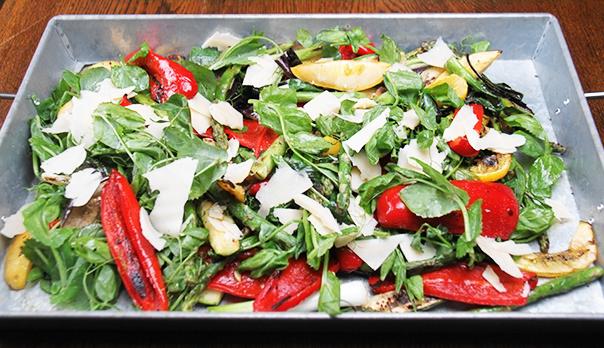 Billedet viser et fad af grillede grøntsager med parmesanost.