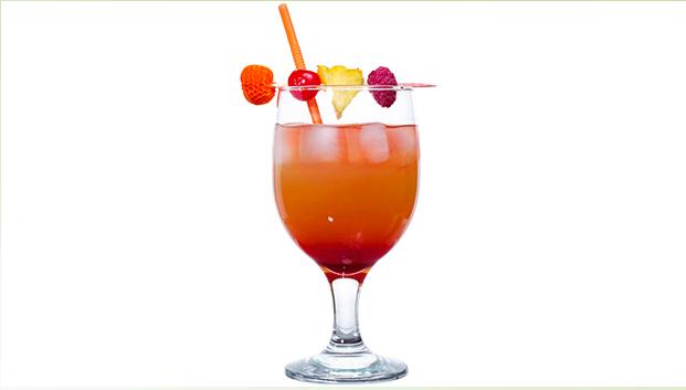 Billedet viser et glas Bermuda Rum Swizzle pyntet med bær og ananas.