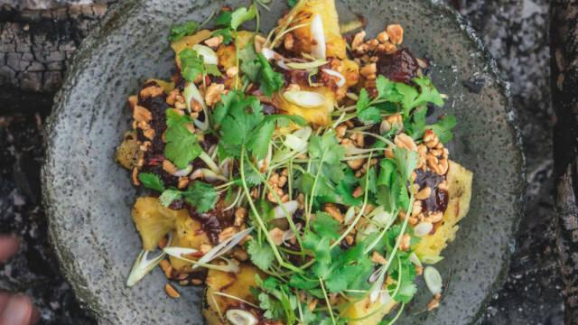 En tallerken med grillet ananas og ristede peanuts