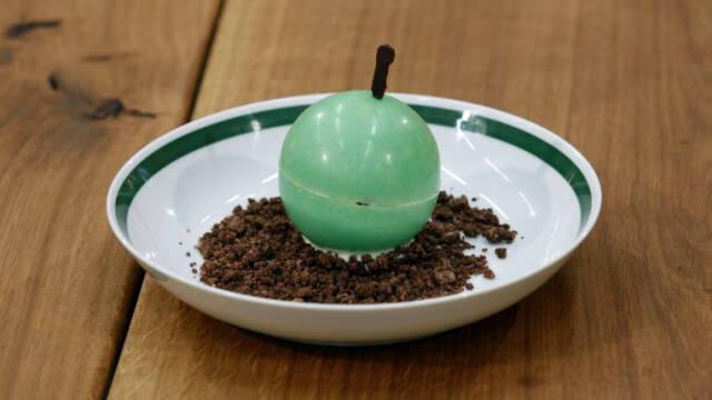 En æblekage-dessert i en chokoladekugler, der forestiller et æble.