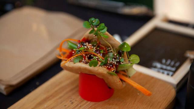 En bao med grøntsager, pulled chicken, urter, chilisovs og sesam