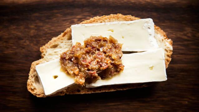 franskbrødsskive på træbord med ost og syltetøj