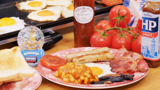 En tallerken med baked beans, pølser, bacon og tomat ved siden af
