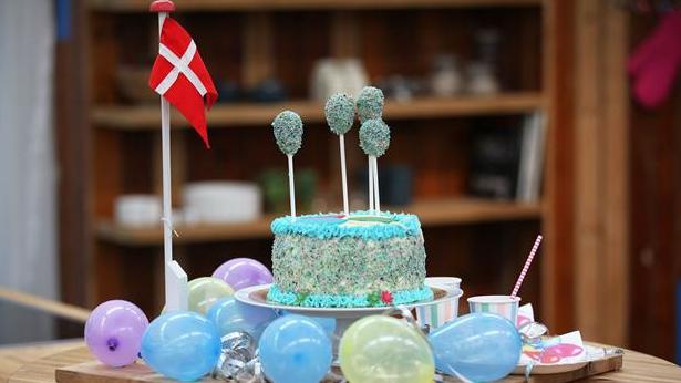 Fødselsdagskage med farver og balloner på toppen