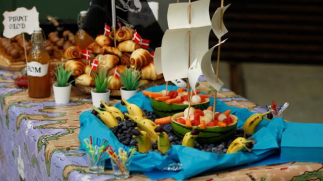 Billedet viser et flot pyntet bord med pirattema, pølsehorn og et blåt frugtfad med halve meloner som skibe og bananer, der ligner delfiner.