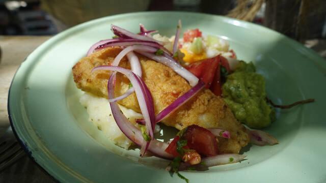 Paneret barracuda med avokado og rødløg på hvid tallerken.