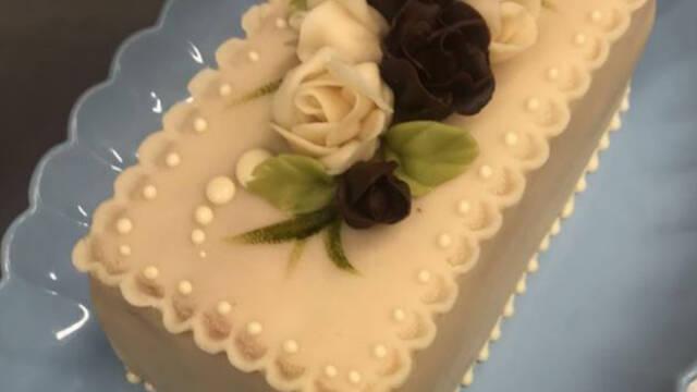 battenberg-kage dekoreret med sort og hvide blomster på blåtfad
