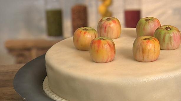 Æblelagkage med fyldige marcipan æbler på toppen.