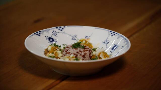 Hvid, mønstret dyb tallerken med veganske boller i karry på et træbord.