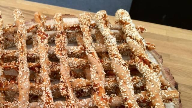 Billede af lækre breadsticks med bacon og tomat, rullet i sesam og stablet flot.