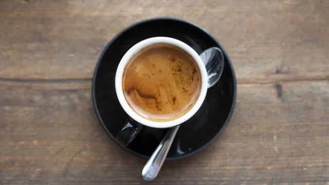 En kop smørkaffe i en hvid kop på en sort underkop.