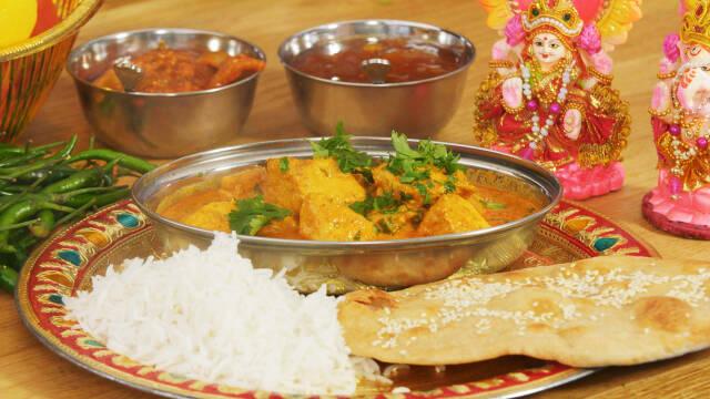En tallerken med et metalfad med chicken tikka masala og ris og naanbrød ved siden af.
