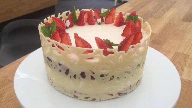 Rund kage med jordbær og hvidt chokoladebånd