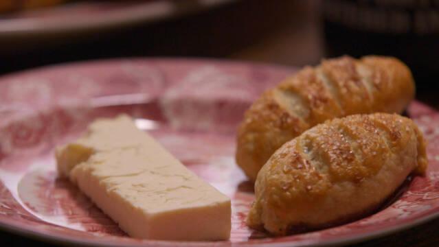 Lyserød tallerken med to eccles cake småkager og et stykke ost