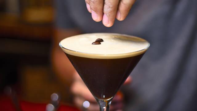 Et højt glas med espresso martini og et par kaffebønner ovenpå.