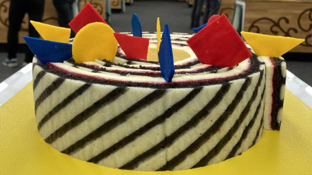 Sort-hvid kage med farverige former på toppen