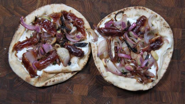 To fladbrødspizzaer på mørkt skærebræt.