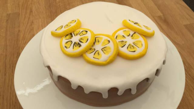 Lemon Drizzle Cake pyntet med fondant på en hvid tallerken.