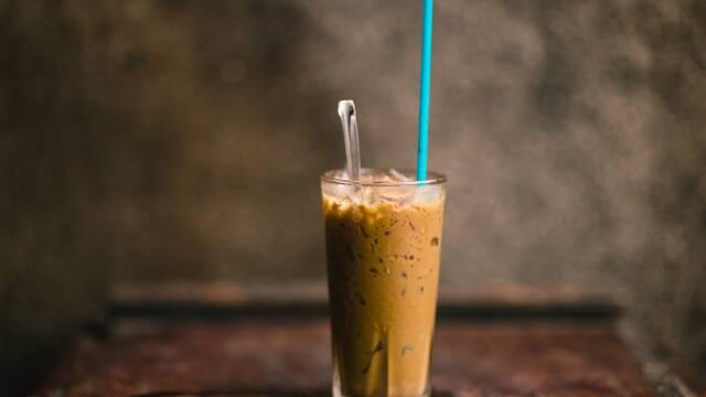 Billede af en iskaffe i et højt glas med blåt sugerør