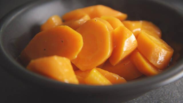 Glaserede gulerødder i sort skål