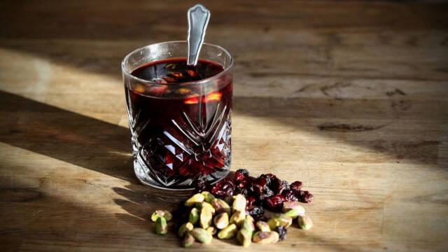 Gløgg i gennemsigtigt glas med pistacienødder på et træbord