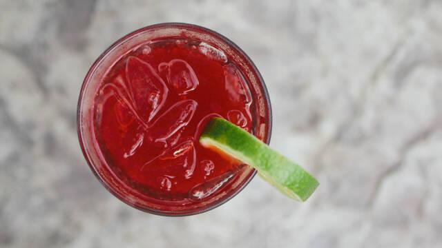 Rød drink med lime på gråt bord.