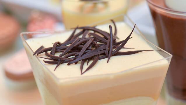 Hvid chokolademousse i firkantet glasskål med chokoladestrimler på toppen