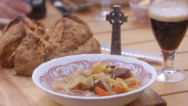 Irish stew i hvid og lyserød tallerken med brød