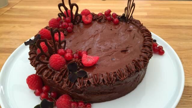 Billede af fyldig chokoladekage med hasselnøddeknas og friske bær på toppen