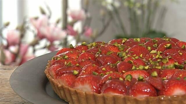 Jordbærtærte med citronfromage på grå tallerken med blomster i baggrunden