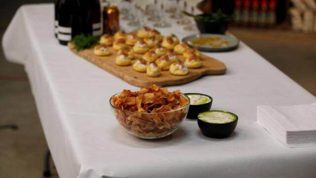 Et bord med hvid dug og en stor skål med hjemmelavede jordskokkechips og hjemmelavet dip i to skåle ved siden af