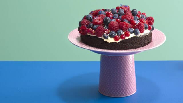 En kakaokage på et højt fad med hindbær og blåbær ovenpå