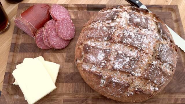 Rustisk grovbrød serveret med smør og vildtspegepølse.