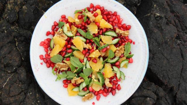 Farvestrålende salat med granatæbler på hvid tallerken