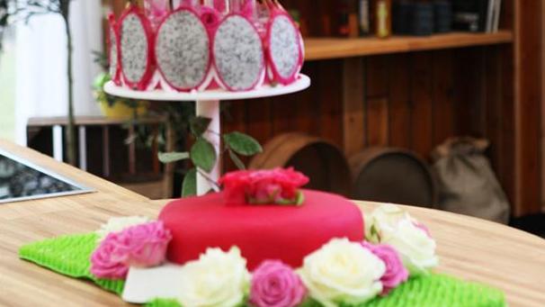 Kage med grape- og rosenmousse pyntet med dragefrugt