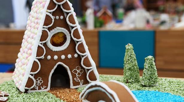 Billede af smukt kagehus af peberkagedej med marengstag og glasur.