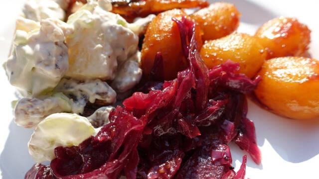 Brunede kartofler med rødkål på hvid tallerken.
