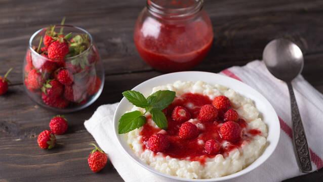 Risengrød i hvid tallerken med jordbær på toppen