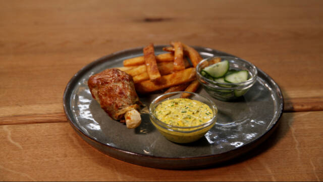 Billedet viser en mørkegrå tallerken på et træbord med et vegansk kyllingelår, dressing, syltede agurker og pomfritter på.