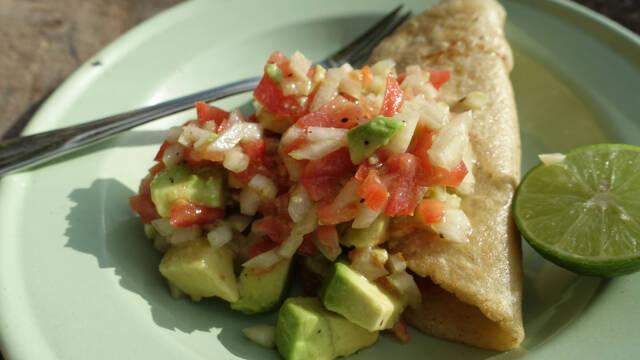 Tacos med fyld på grøn tallerken med gaffel og lime.