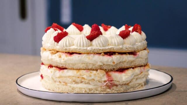 Lagkage med hindbær og flødeskum på hvid tallerken
