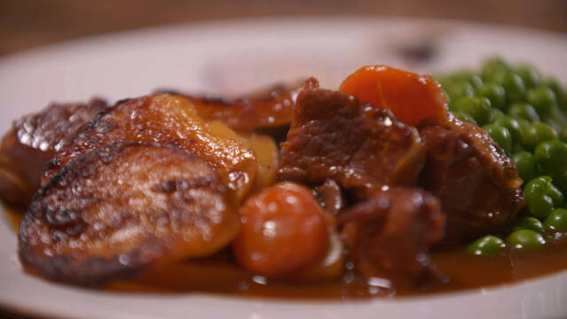 Tallerken med ærter, lammekød, kartofler og gulerødder.