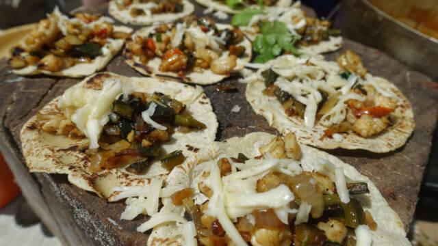 Tacos med languster og stegt peber på et stenbord.