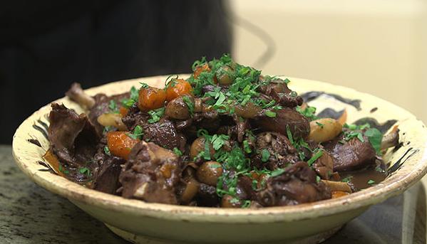 Lapin au vin i dyb tallerken med gulerødder og hvidløg.