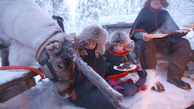 Familie spiser rensdyrgryde ude i det fri